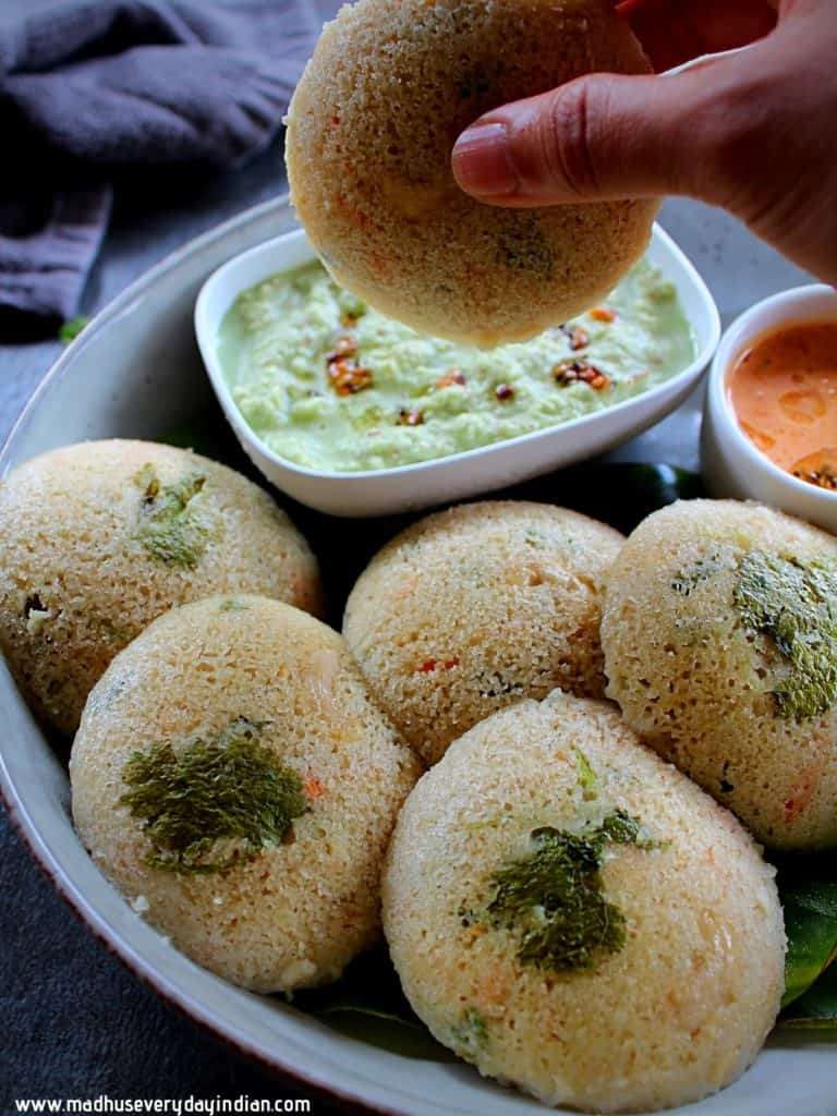 oats rava idli held in a hand trying to dip in the chutney