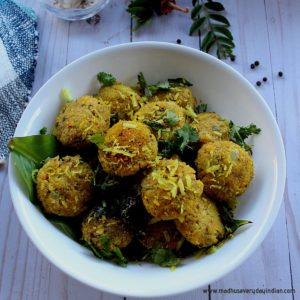 steamed chana dal vada served in a white bowl with a tempering of mustard and coconut