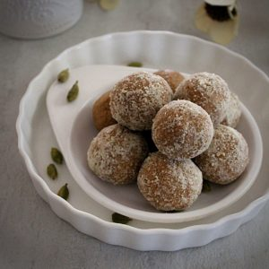 almond ladoo made with almond flour arranged in a double white place and garnished with cardamom.