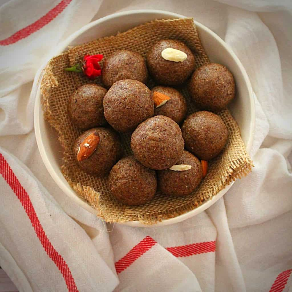 flax seed ladoo served in a white bowl garnished with almonds