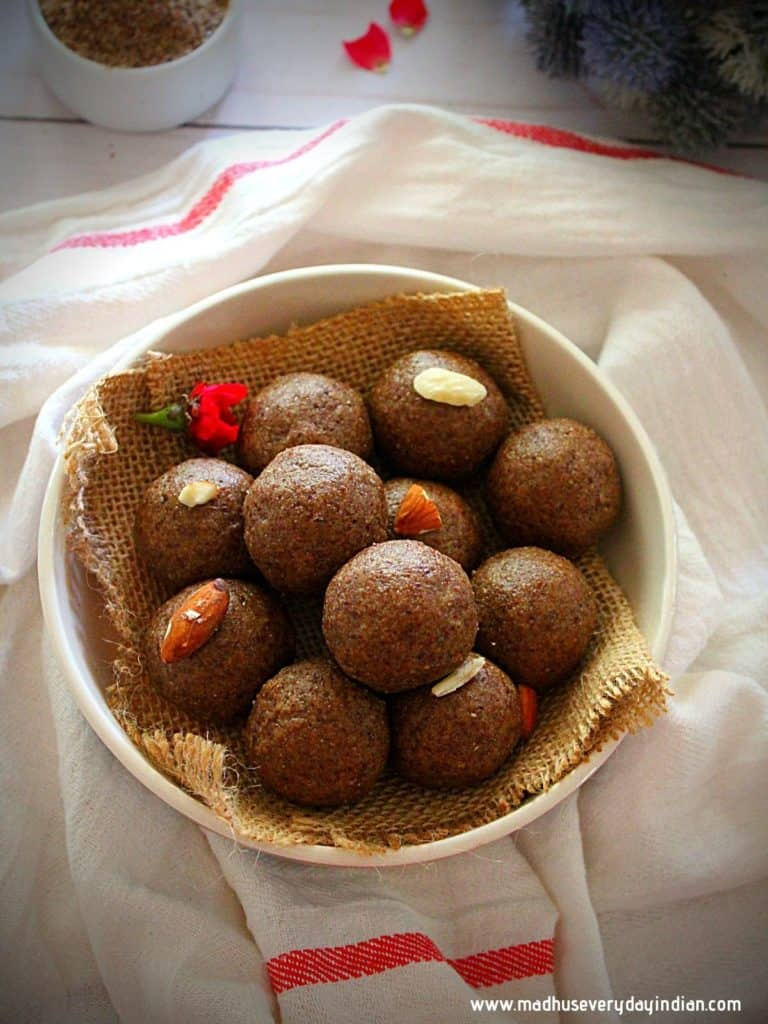 flax seed ladoo served in a white bowl garnished with almonds and powdered fax seeds in the back.