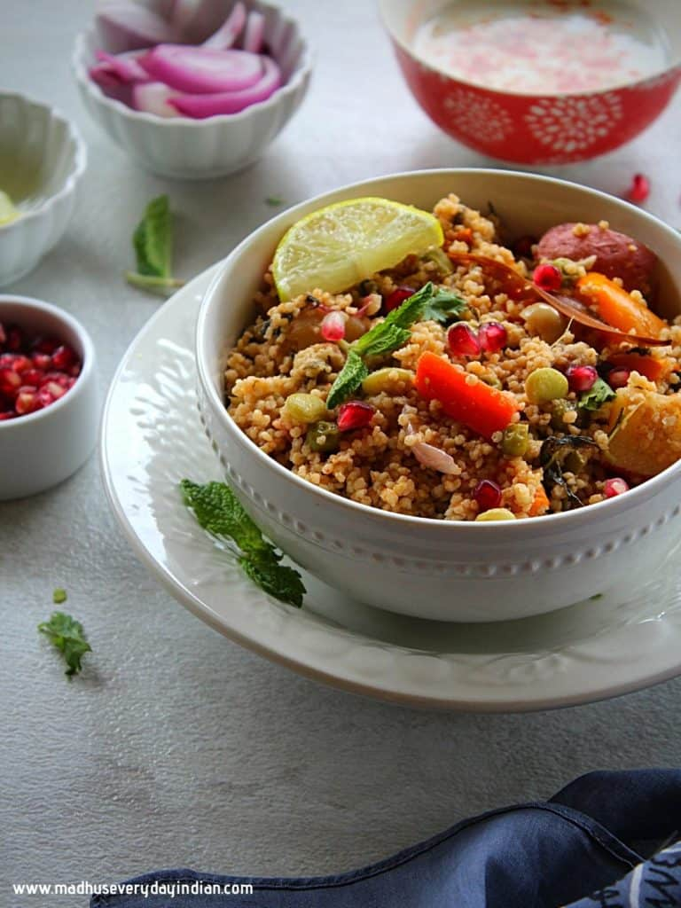 millet pulao served in a white bowl with lemon wedge, onion, pomegranate and yogurt