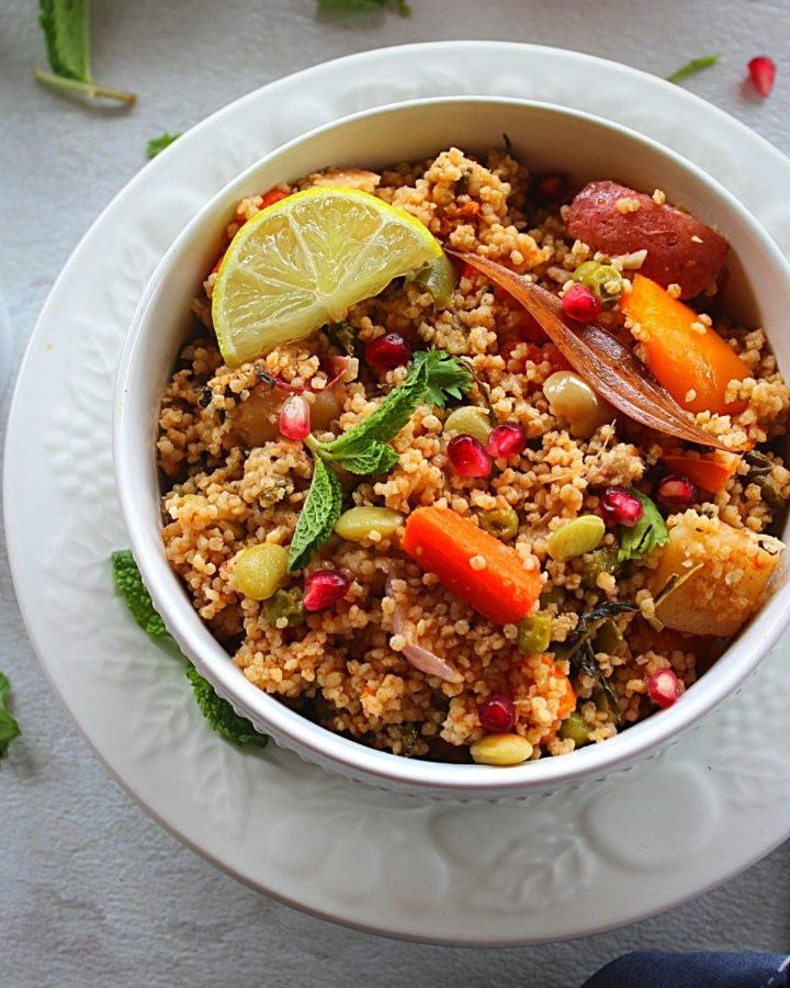 millet pulao served in a white bowl with lemon wedge, onion, pomegranate