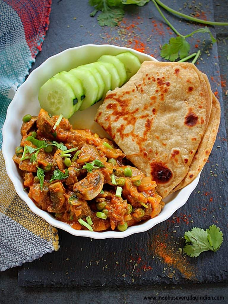 mushroom curry served with sliced cucumber and home made paratha in a white plate.