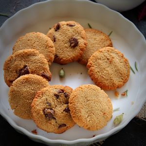 almond flour cookies placed in w hite plate with garnish of cardamom