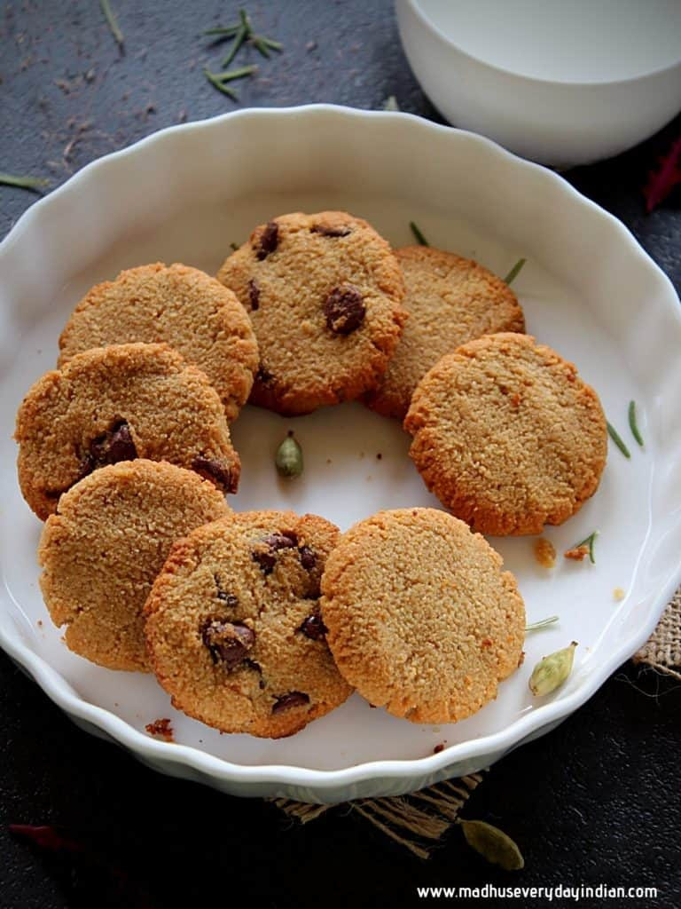almond flour cookies with chocolate chips placed in a white plate with a cup of milk