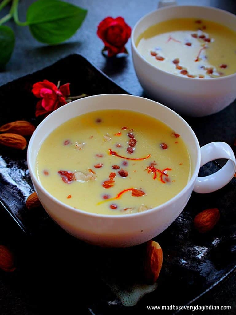 badam milk served in white tea cups topped with saffron and nuts