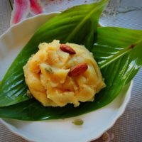 badam halwa served with green leaves towhole almonds, saffron and cardamom