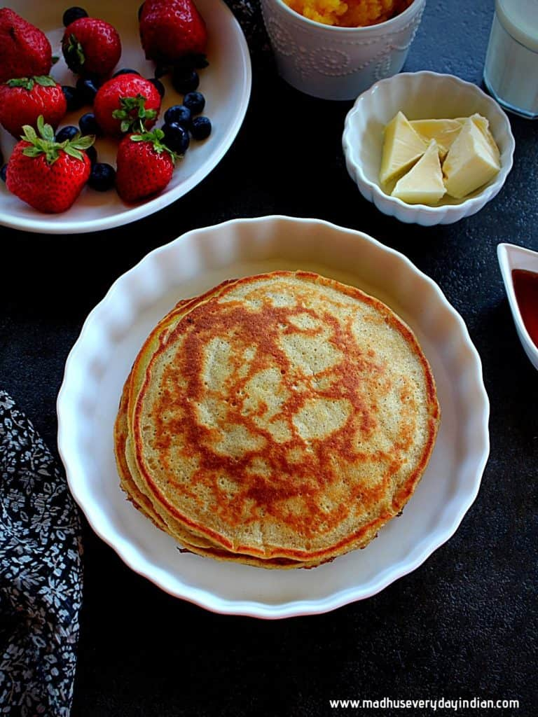 stacked pumpkin pancakes in a white plate and on the side are butter, berries and syrup
