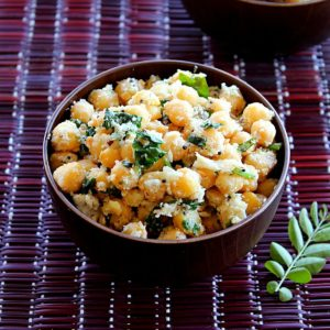 chana sundal served in a brown bowl with curry leaves on the side