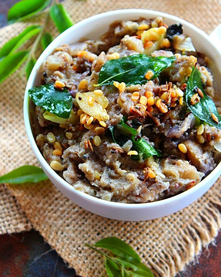 eggplant chutney or vankaya pachadi served in a white tea cup with curry leaves and tempering of mustard and urad dal on the top