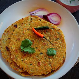 oats paratha served with pcikle, raita and onion, green chili