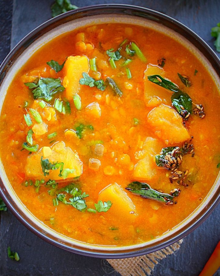 pumpkin dal served in a brown bowl garmished with cilantro and atempering of mustard, cumin and curry leaves.