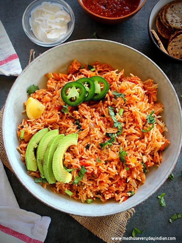 spanish rice served in a white plate with guacamole and jalapeno