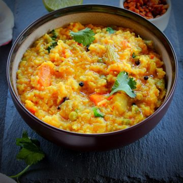 khichdi served in a brown bowl and on the side are garlic pickle and lemon