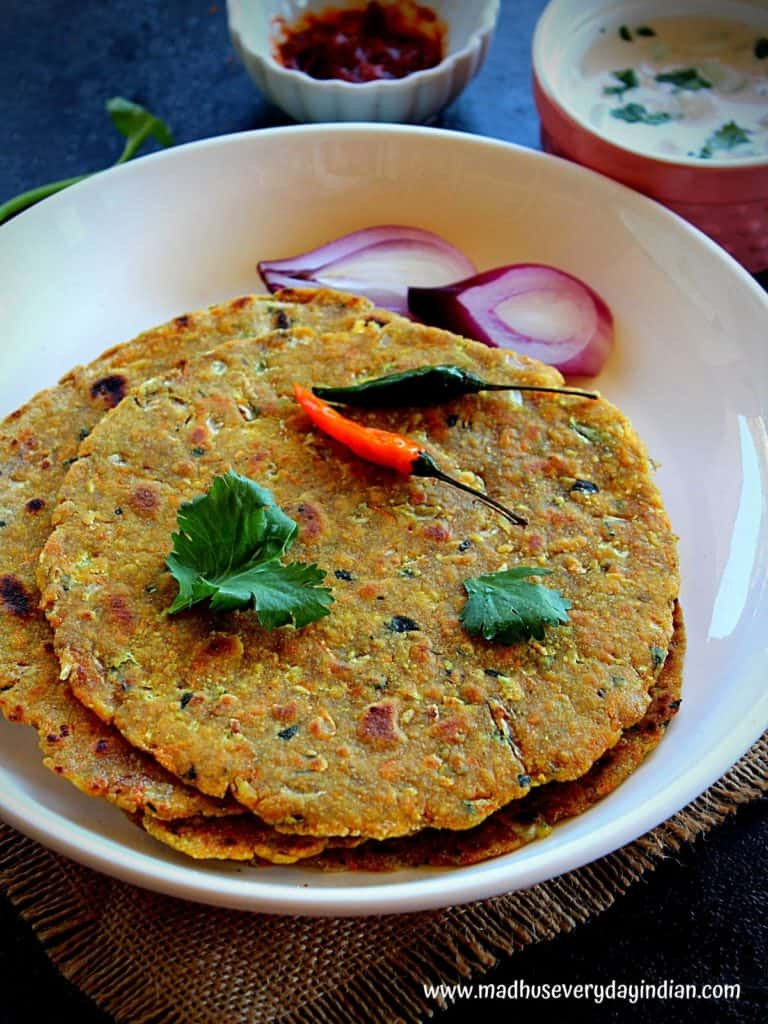 oats masala paratha served with pcikle, raita and onion, green chili
