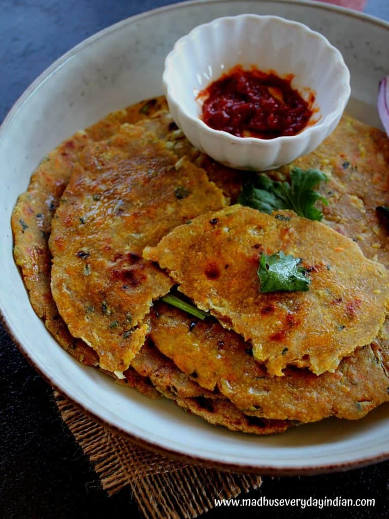 oats masala paratha served in a plate , few torn pieces of pararha served with ginger pickle,