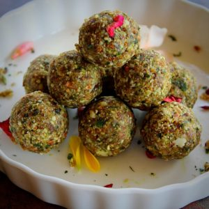 paan coconut nuts ladoo served in a white bowl garnished with rose petals