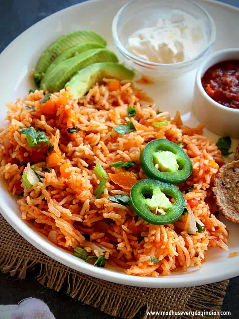 spanish rice served in a white plate with guacamole and jalapeno, sour cream and chips