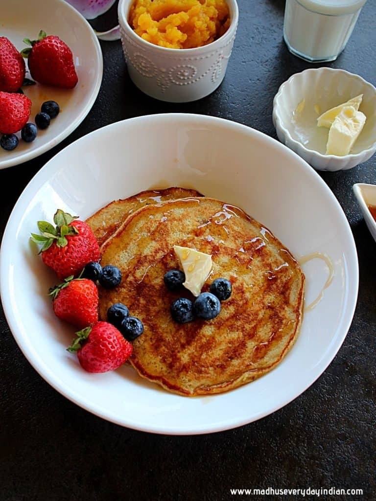 pumpkin pancakes drizzled with maple syrup and garnished with butter and berries