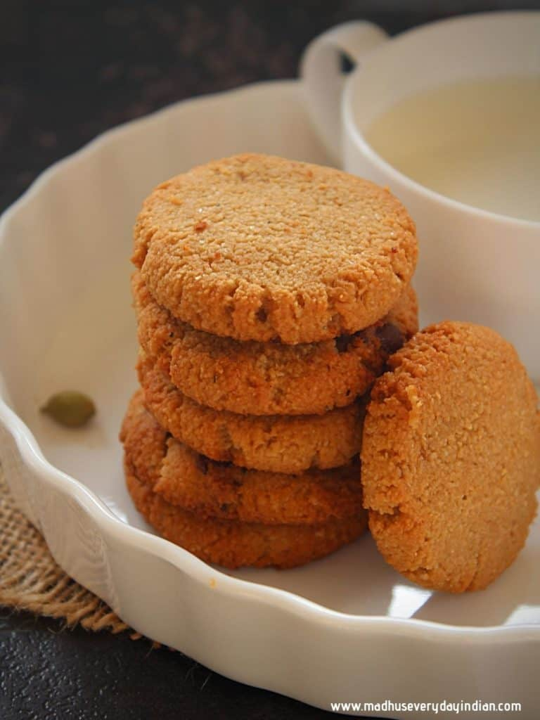 clmond flour cookies staced on each other and served with a cup of milk
