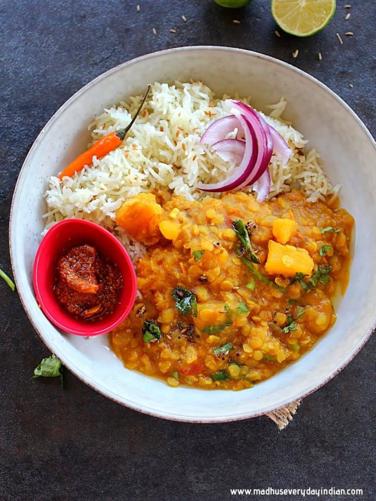 pumpkin dal served with cumin rice, lemon pickle, onion and chili in a white plate and elmon on the side.