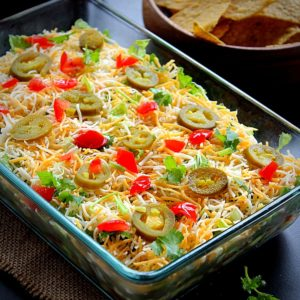 7 layer bean dip served in a glass tray garnished with jalapeno, tomato and coriander and served with tortilla chips and salsa