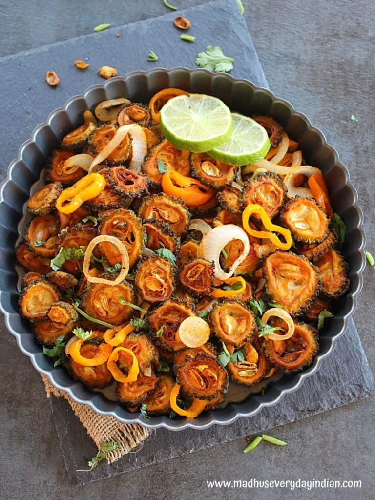 Baked sweet and sour karela served in a pan garnished with cilantro and some lime slices