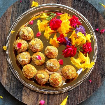 carrot ladoo served in a sliver plate with colored flowers