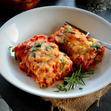 2 veggie lasagna rolls ups served in a white plate garnished with fresh herbs