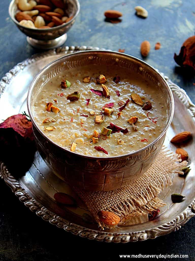 quinoa kheers erved in a large silver bowl garnished with rose petals, saffron and nuts