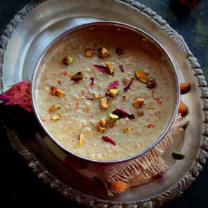 quinoa kheers served in a large silver bowl garnished with rose petals, saffron and nuts