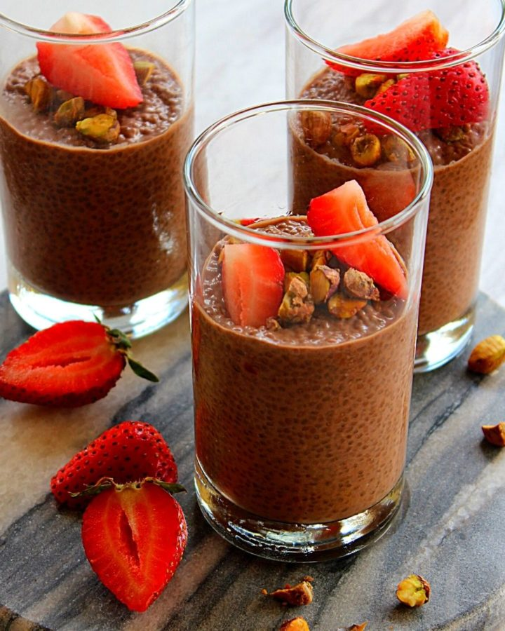 chocolate chia pudding served in three glass cups topped with pistachio and strawberry