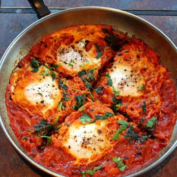 Indian style Shakshuka served in a steel saute pan garnished with cilantro