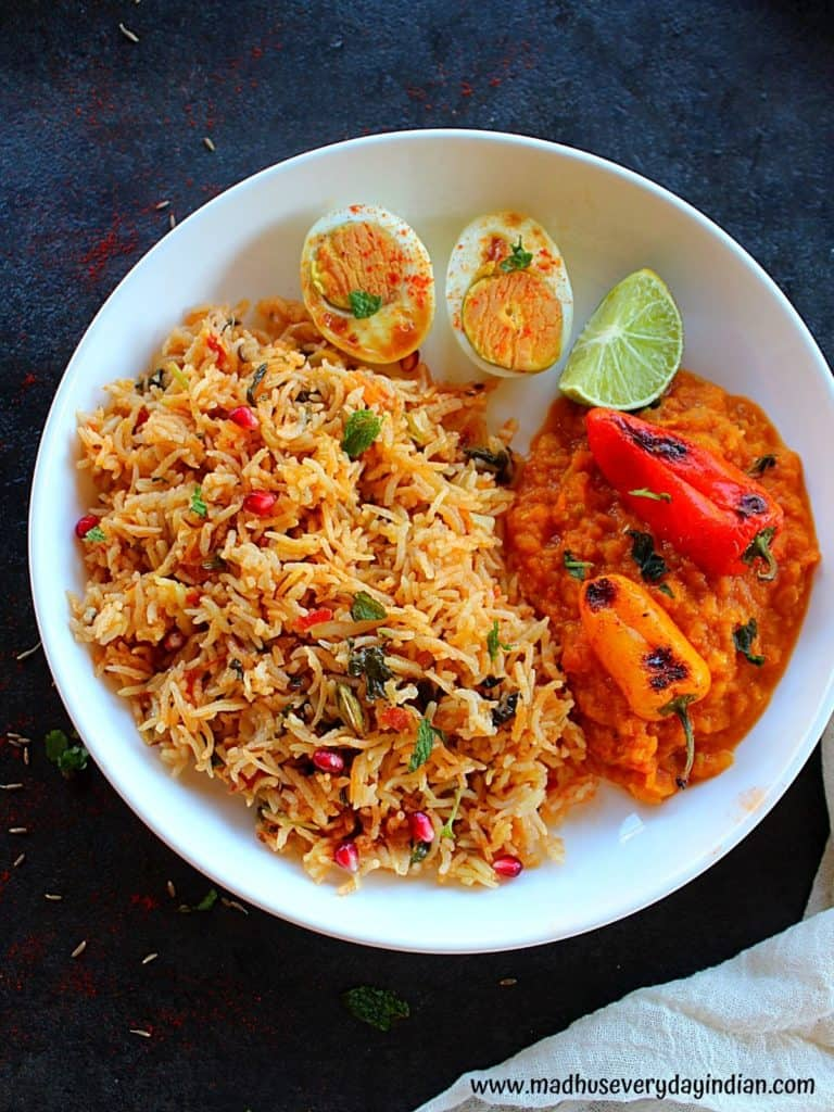 plain biryani served in a  white plate with boiled eggs, lime wedge and bell pepper curry