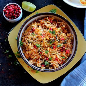 plain biryani served in a brown bowl garnished with pomegranate and served with boiled eggs and mini bell pepper curry