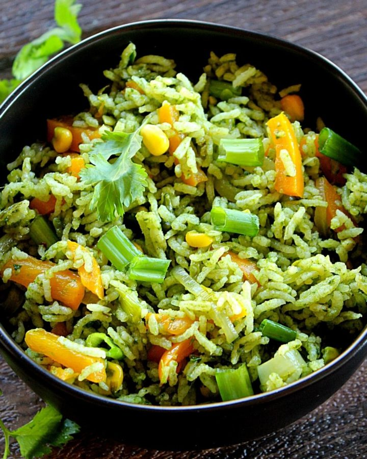 indian style spinach fried rice served in a black bowl garnished with coriander leaves