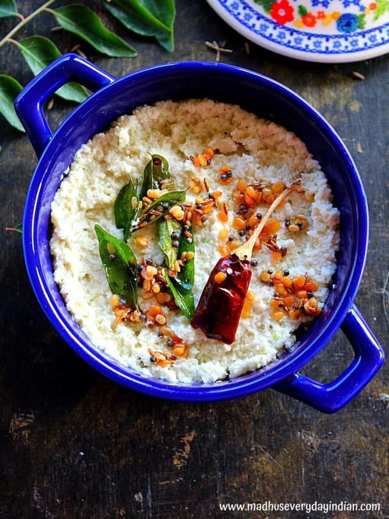 desiccated coconut chutney served in a blue bowl with a temeoring of mustard seedsm dal, curry leaves and dry red chili