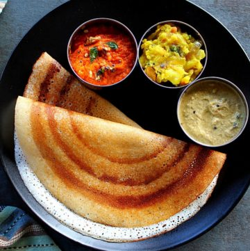 rice flour dosa served in a black palte with two chutney's and potato fry