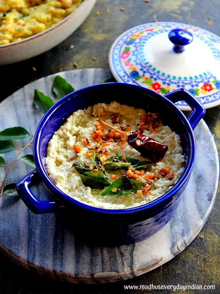 desiccated coconut chutney served in a blue bowl with a tempering made of  of mustard seeds, urad dal, curry leaves and dry red chili
