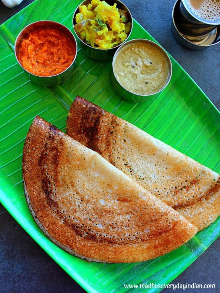 rice flour dosa with urad dal served ina green leaf plate with 2 chutneys and potato fry