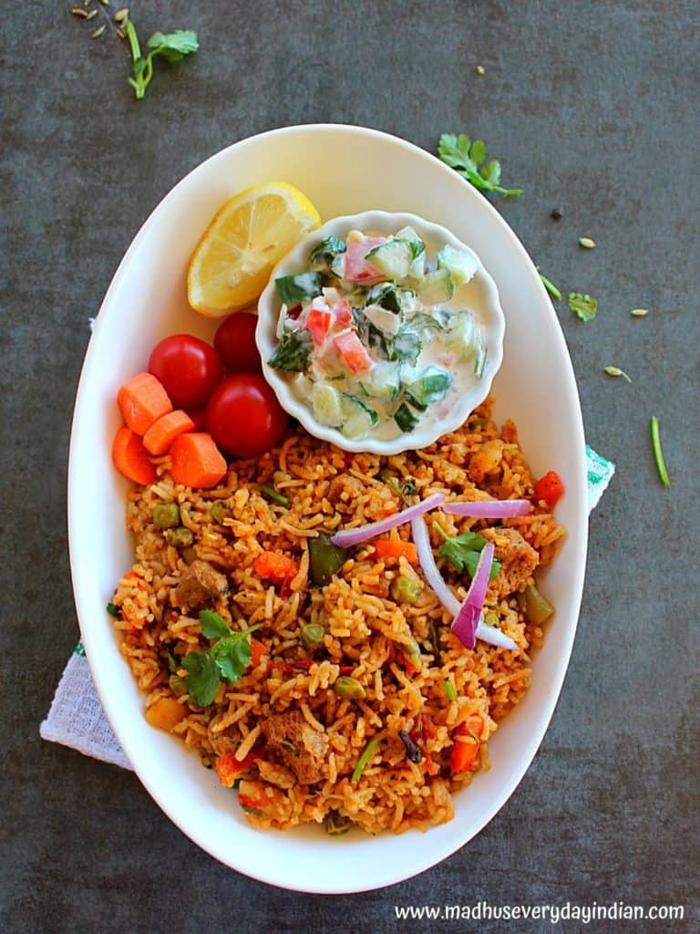 meal maker biryani serevd in a white oval bowl with raits, tomato, carrot and lemon wedge