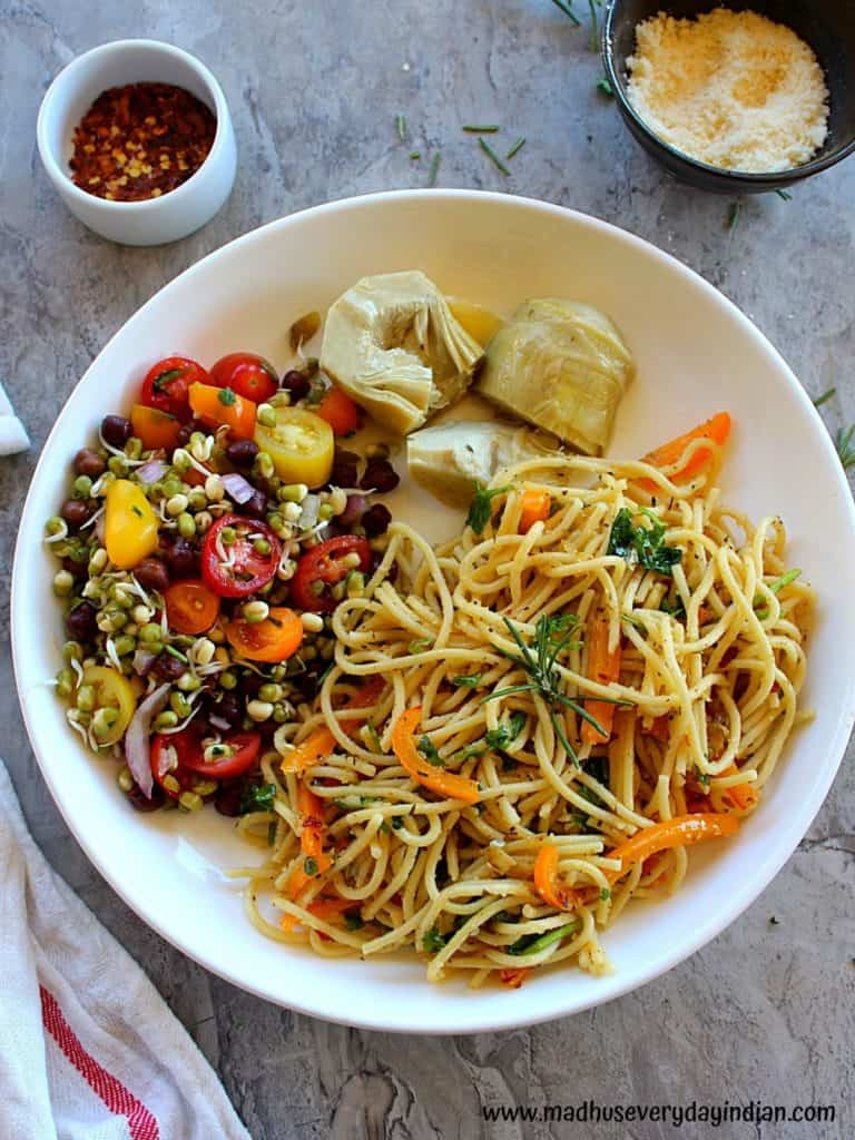 spaghetti aglio e olio made in the instant pot is served with salad and marinated artichokes.