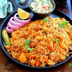 soya chunks biryani served in a cast iron pan with raita, onion circles, chili and lemon wedge