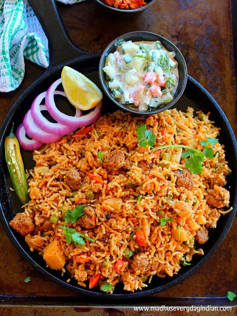 soya chunks biryani served in a cast iron pan with raita, onion circles, chili and lime wedge
