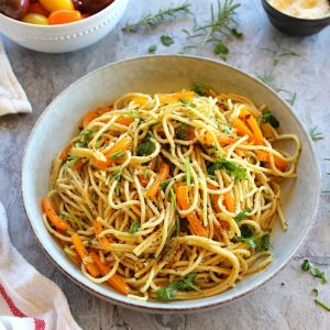 spaghetti with garlic and olive oil served in a large plate garnished with parsley and on the side are parmesan cheese and cherry tomato