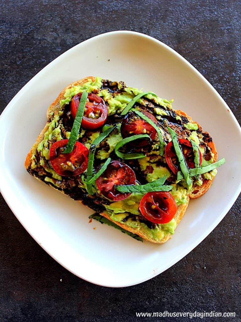 tomato basil avocado toast with balsamic drizzle served in a white plate