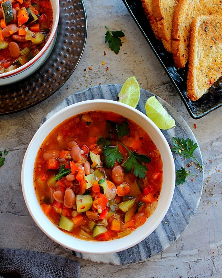 vegetable soup with pinto beans served in a large bowl garnished with parsley and lemon