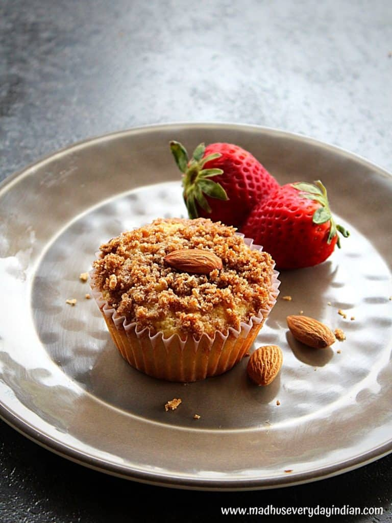 one almond flour muffin served in a plate with strawberry and 2 whole almonds