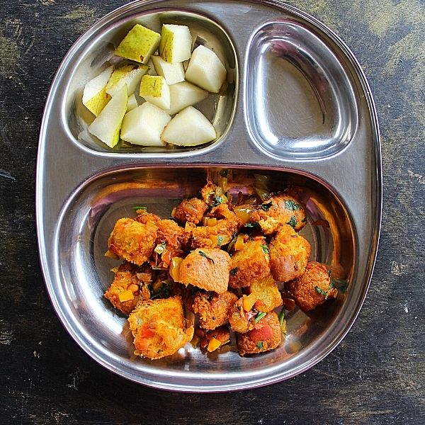 bread upma served with pear pieces served in a steel partition plate